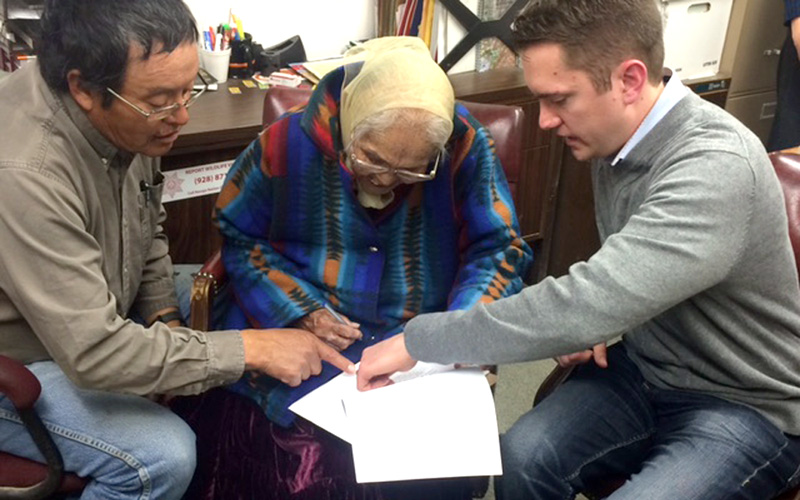 A client signs her will at Ramah, New Mexico, with the assistance of interpreter Kee Lee and student John Gatewood